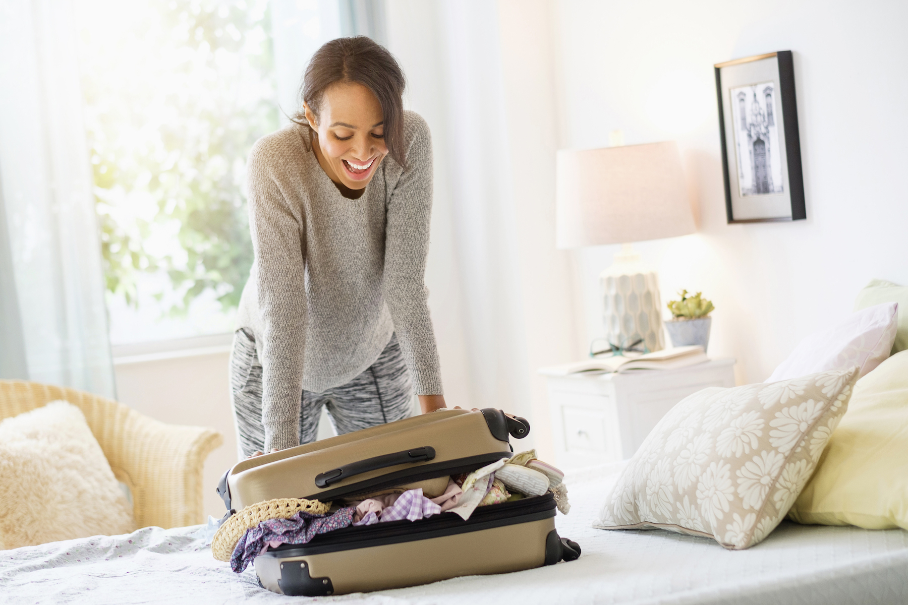 Woman packing suitcase on bed