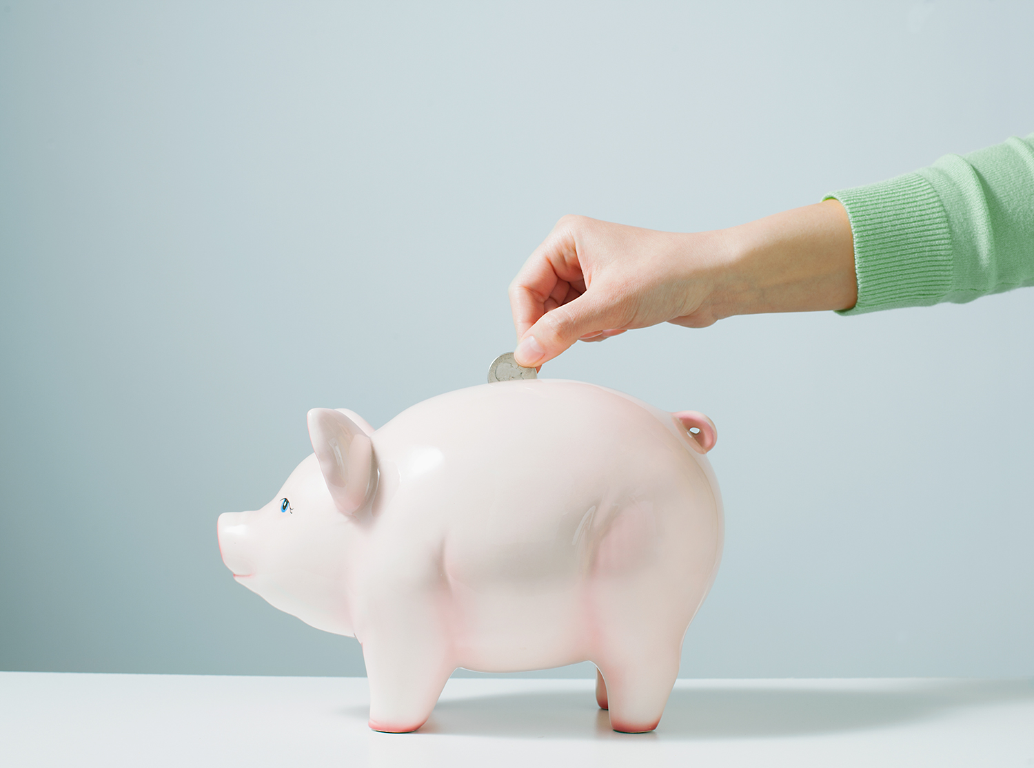 Hand Placing Coins in Piggy Bank
