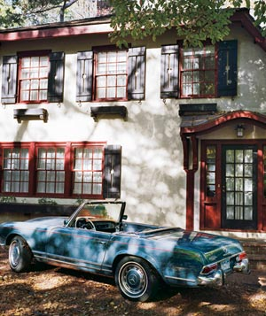 Blue convertible in front of white and red house