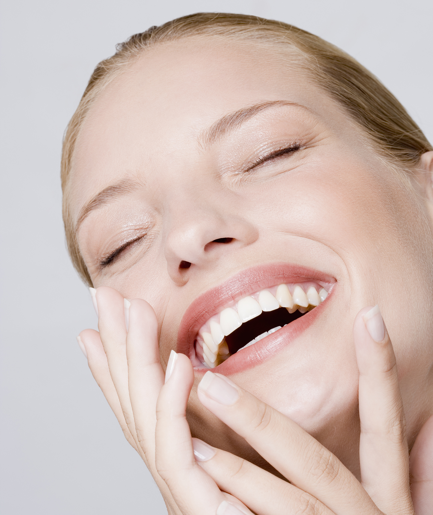 Woman laughing with hands on face