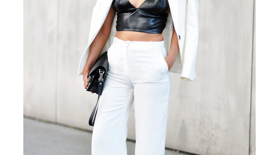 Woman wearing black leather bralette with white suit