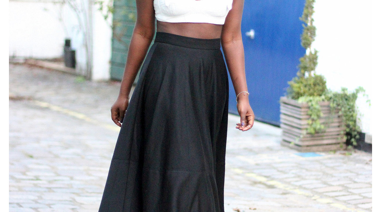 Woman wearing white leather bralette with black full skirt