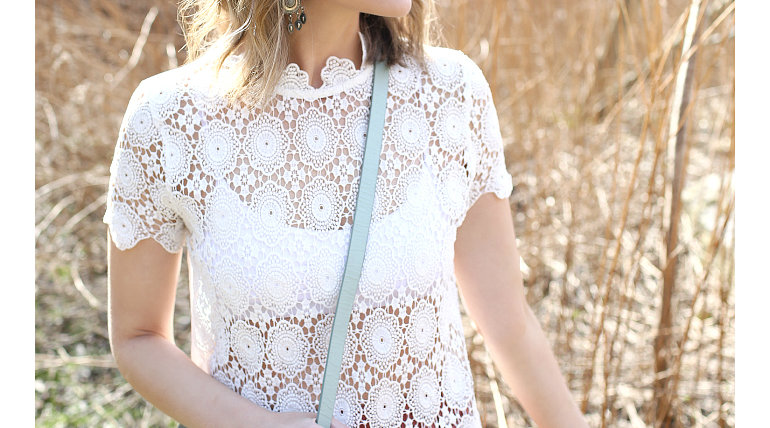 Woman wearing bralette under white scalloped lace top