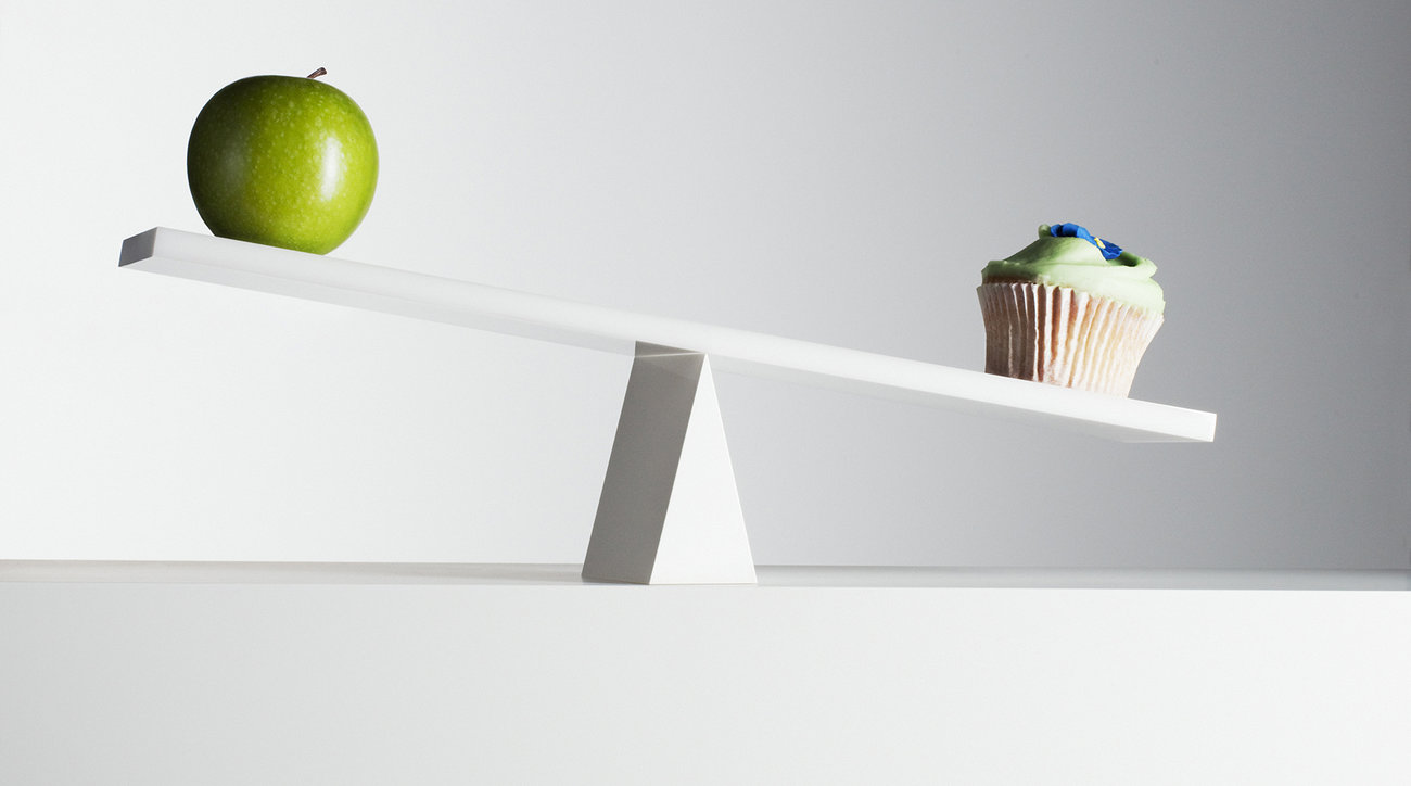 Apple and cupcake on seesaw