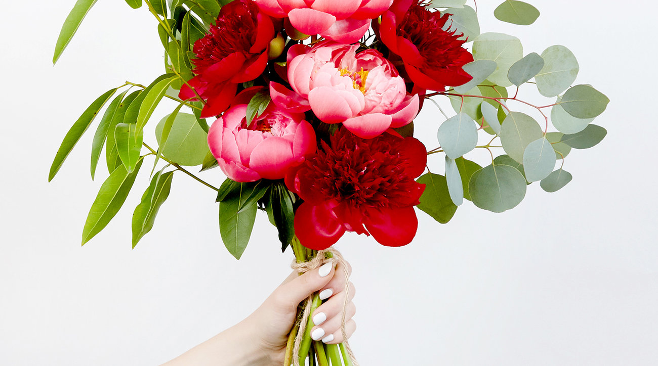 Hand holding bouquet of peonies