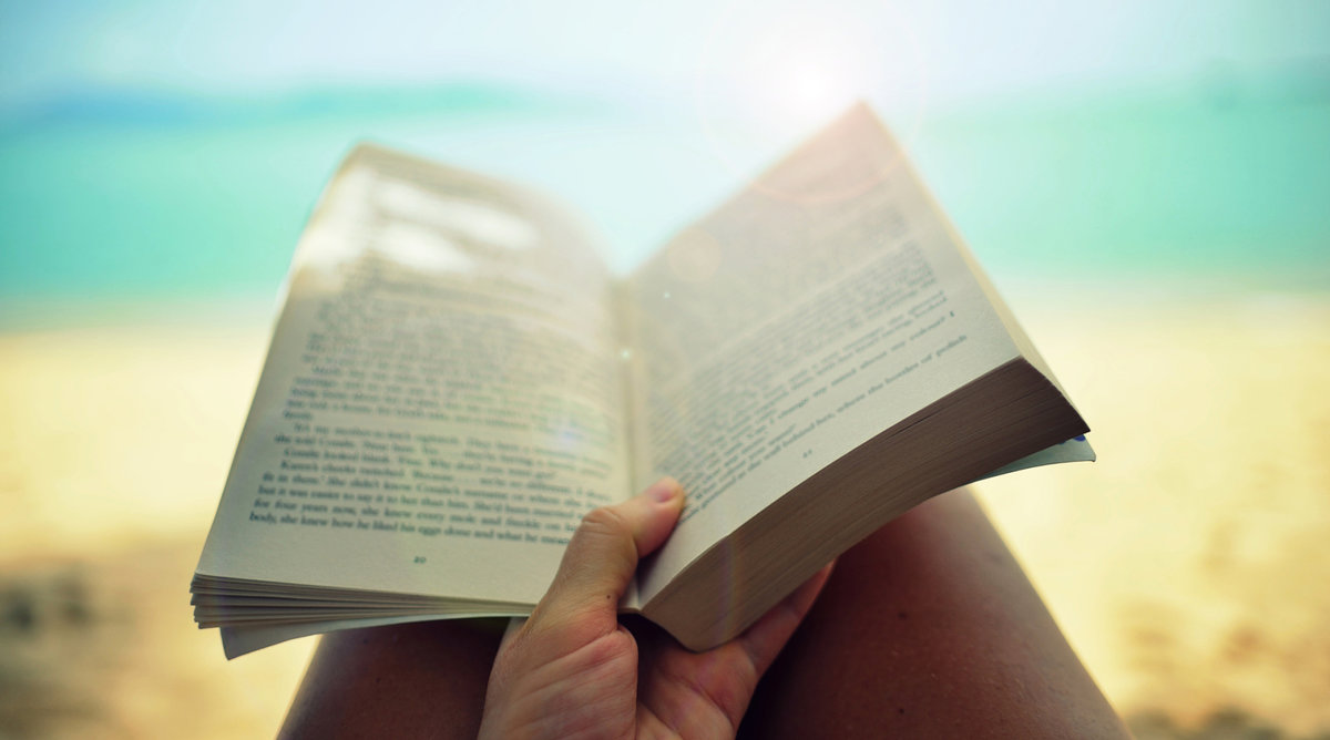 woman reading paperback book on beach
