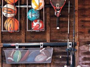 Basket balls, racquets, and other sports equipment on hooks in a garage