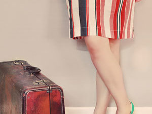 Woman standing beside a vintage suitcase