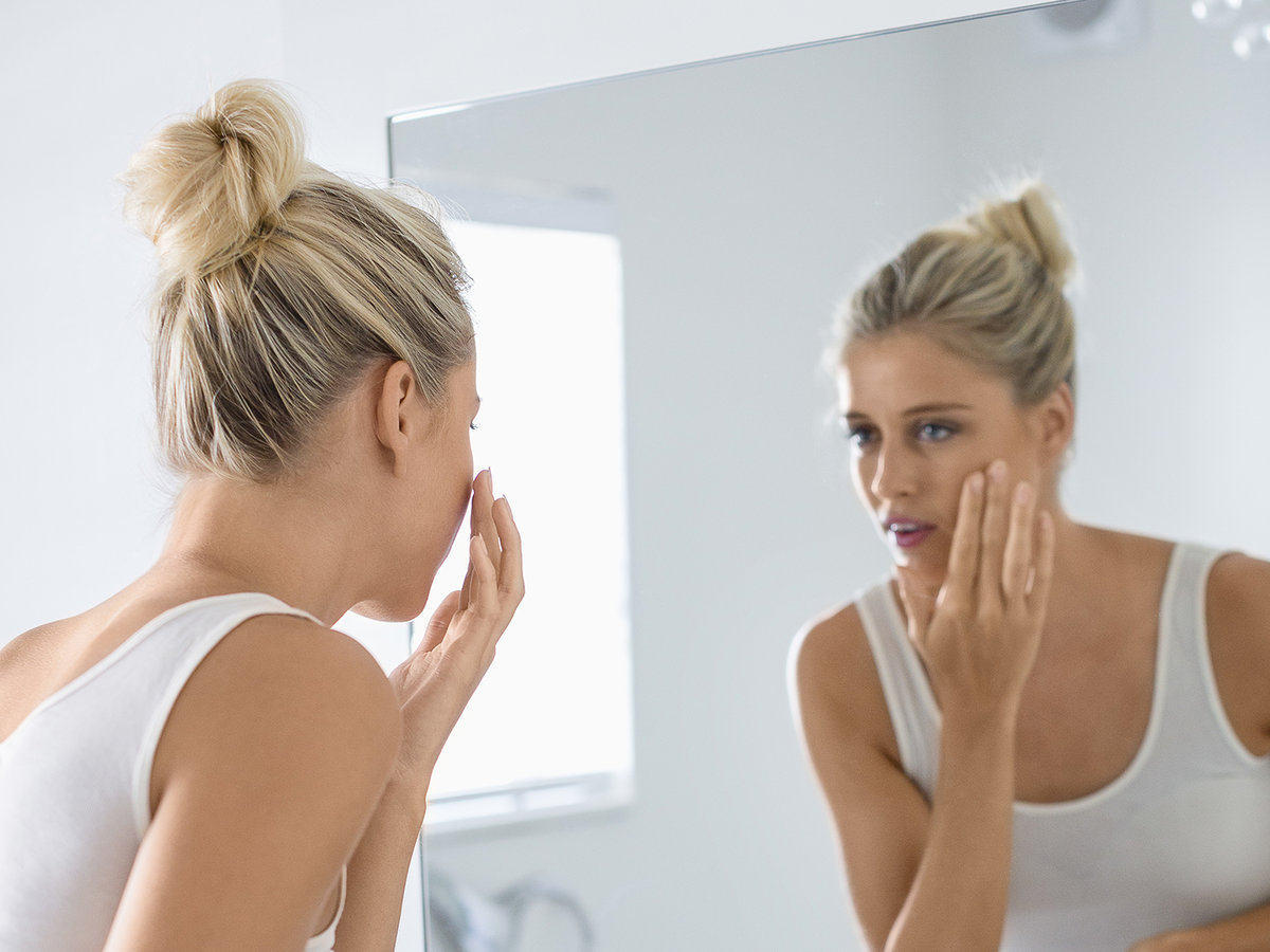 Woman Looking in the Mirror Trying to Look Younger
