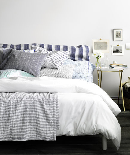 Bed with blue and white cushy pillows