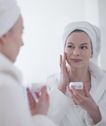 A Woman Applies an Anti-Aging Product While Looking in the Mirror
