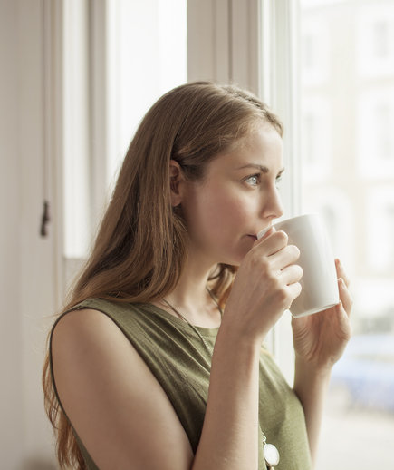Woman Looking Out the Window Drinking Coffee