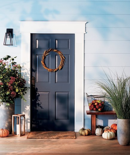 Classic style front door with pumpkins and wheat wreath