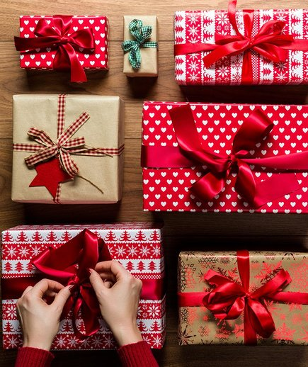 Woman's hand trying ribbon on gift