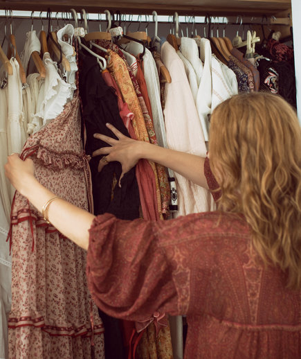 Closet Purge How To, Woman looking at clothing in closet