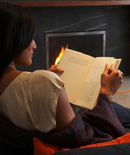 woman reading book by fire
