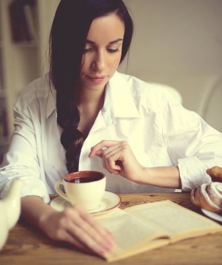woman reading at home in kitchen