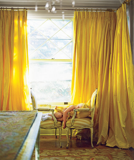 Child sleeping on 2 chairs in front of heavy golden drapes