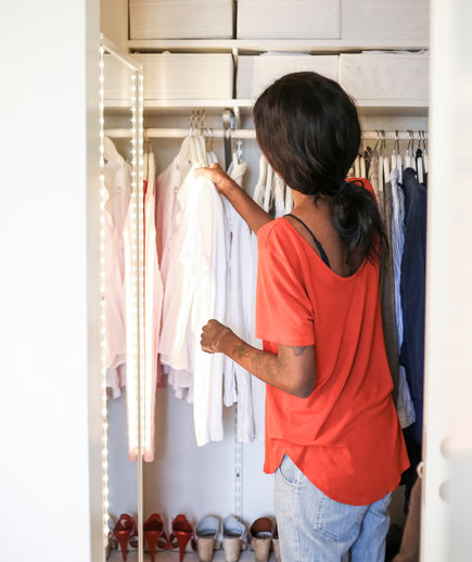 Fall and winter organizing must-dos woman hanging clothes in closet