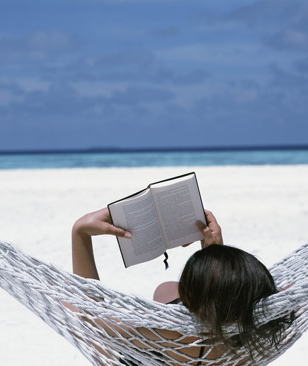 Woman reading in a beach hammock