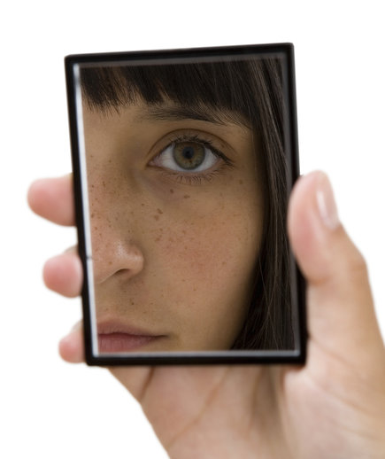 Woman looking at face in hand mirror