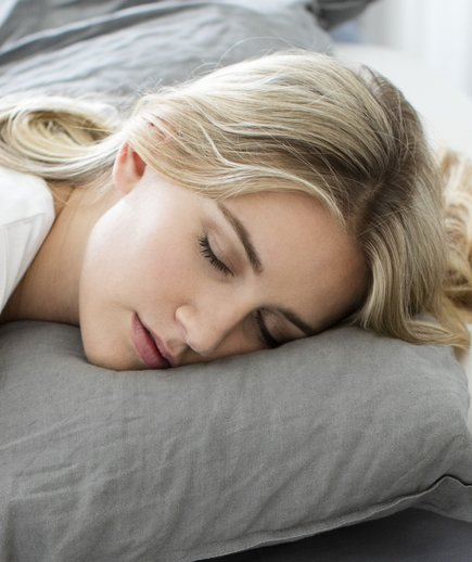 Young woman sleeping after studying tips on how to sleep better.