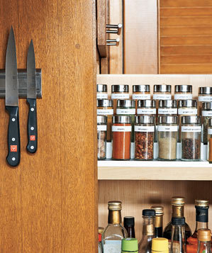 Spices and knives on a magnetic strip in an organized kitchen