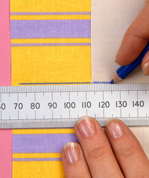 Hands using chalk pencil and ruler to measure curtains