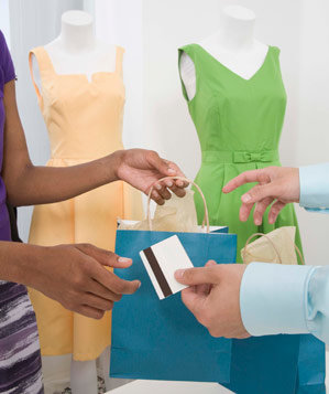 Woman paying with credit card in dress shop
