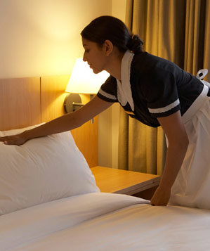 Housekeeper making the bed in a hotel room