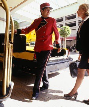 Bellhop carrying a businesswoman's luggage