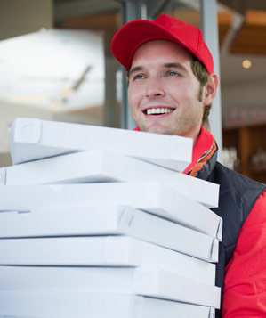 Young man delivering a stack of pizzas