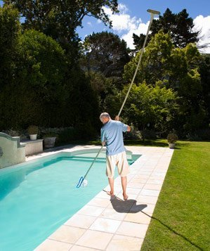 Man cleaning a pool with a skimmer