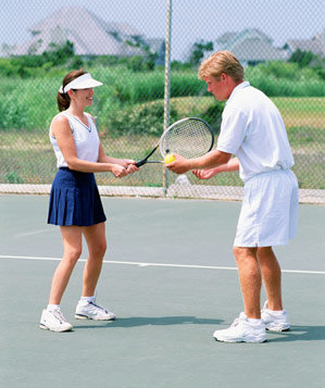 Tennis instructor teaching a student