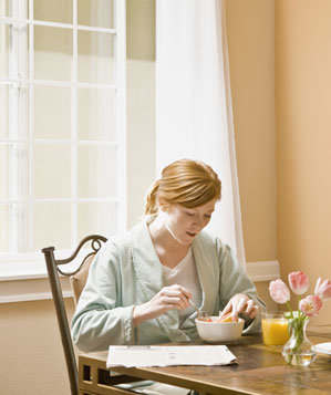 Woman eating breakfast in a bathrobe