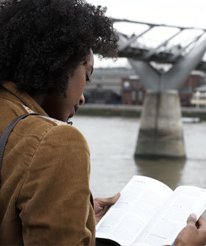 Woman consulting a guide book near a bridge