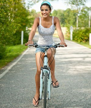 Teenaged girl riding a bicyle, smiling
