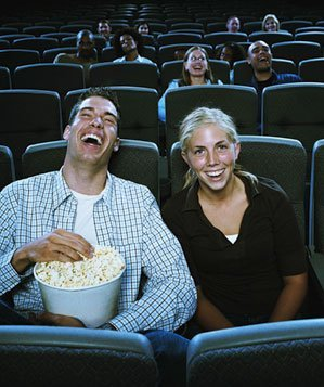 Couple sitting in movie theater, laughing and eating popcorn
