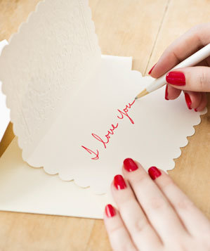 "Woman writing ""I love you"" in a card"