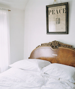 Bed, headboard, framed newspaper