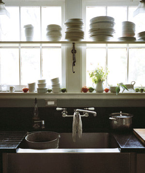 Dishes, plants, and windows above kitchen sink