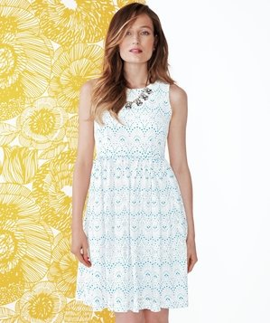 Model wearing white dress with blue embroidery