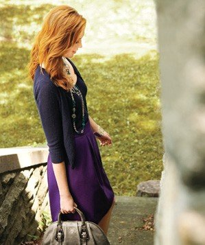 Woman wearing a purple sweater and skirt