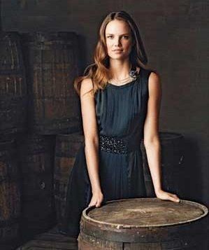 Woman wearing a black bejeweled silk-and-satin dress by BCBG in a winery