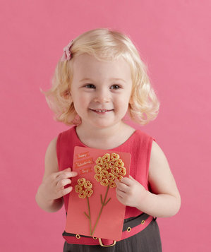 Girl holding Valentine's Day card decorated with dry macaroni