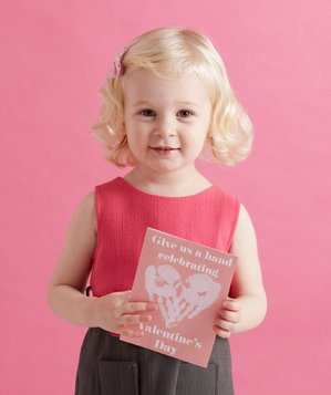 Little girl holding a Valentine's Day card