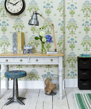 Desk and stool in hallway with floral-patterned wallpaper