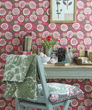 Weathered desk and chair and patterned wallpaper
