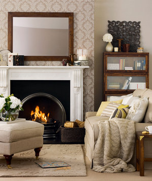 Plush Sofa And Ottoman In Front Of Fireplace