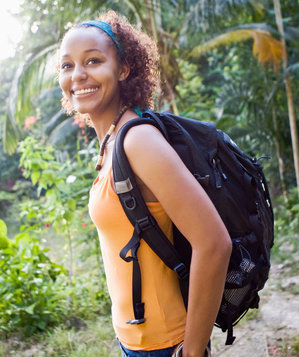 Happy woman hiking with a backpack